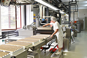 Frau bedient Maschine in der Lebensmittelindustrie - Fabrik zur